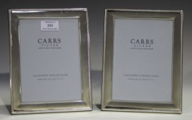 A pair of Elizabeth II silver mounted rectangular photograph frames, each with gadrooned edge,