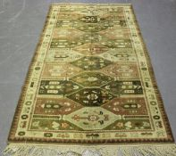 A Turkish rug, mid/late 20th century, the faded compartmentalized field within an ivory border,