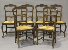 A set of six 20th century French oak framed carved ladder back dining chairs with inset rush