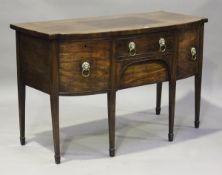 A George III mahogany break bowfront sideboard, fitted with four oak-lined drawers with applied