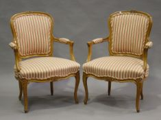 A pair of 20th century Louis XV style beech showframe fauteuil armchairs, upholstered in striped