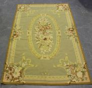 An Aubusson style tapestry rug, late 20th century, the taupe field with an oval floral spray centre,