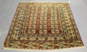 A Tekke rug, West Turkestan, early 20th century, the pale claret field with three columns of guls,