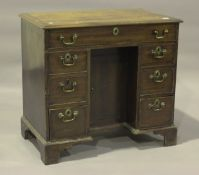 An early 19th century mahogany kneehole desk with crossbanded and ebony line inlaid decoration,