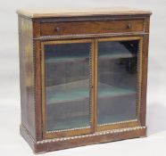 A late Victorian walnut side cabinet, fitted with a drawer above a pair of glazed doors, within bead