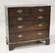 A George III mahogany chest, fitted with two short and three long drawers, raised on bracket feet,