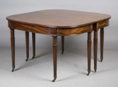 A George III mahogany 'D'-end dining table with central drop-flap section and reeded edge top,