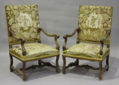 A pair of early 20th century French walnut framed elbow chairs, upholstered in floral woolwork,