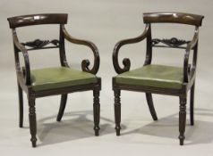 A pair of George IV mahogany bar back elbow chairs with foliate carved centre rails and green
