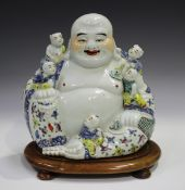A Chinese famille rose enamelled porcelain figure of a seated Buddha, 20th century, with five boy