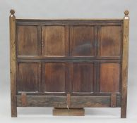 A 17th century and later oak panelled double headboard, height 130cm, width 139cm.Buyer's Premium