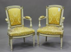 A pair of 20th century Louis XVI style white painted and gilt fauteuil armchairs, upholstered in