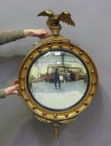 A 20th century Regency style gilt painted circular convex wall mirror with eagle surmount, height