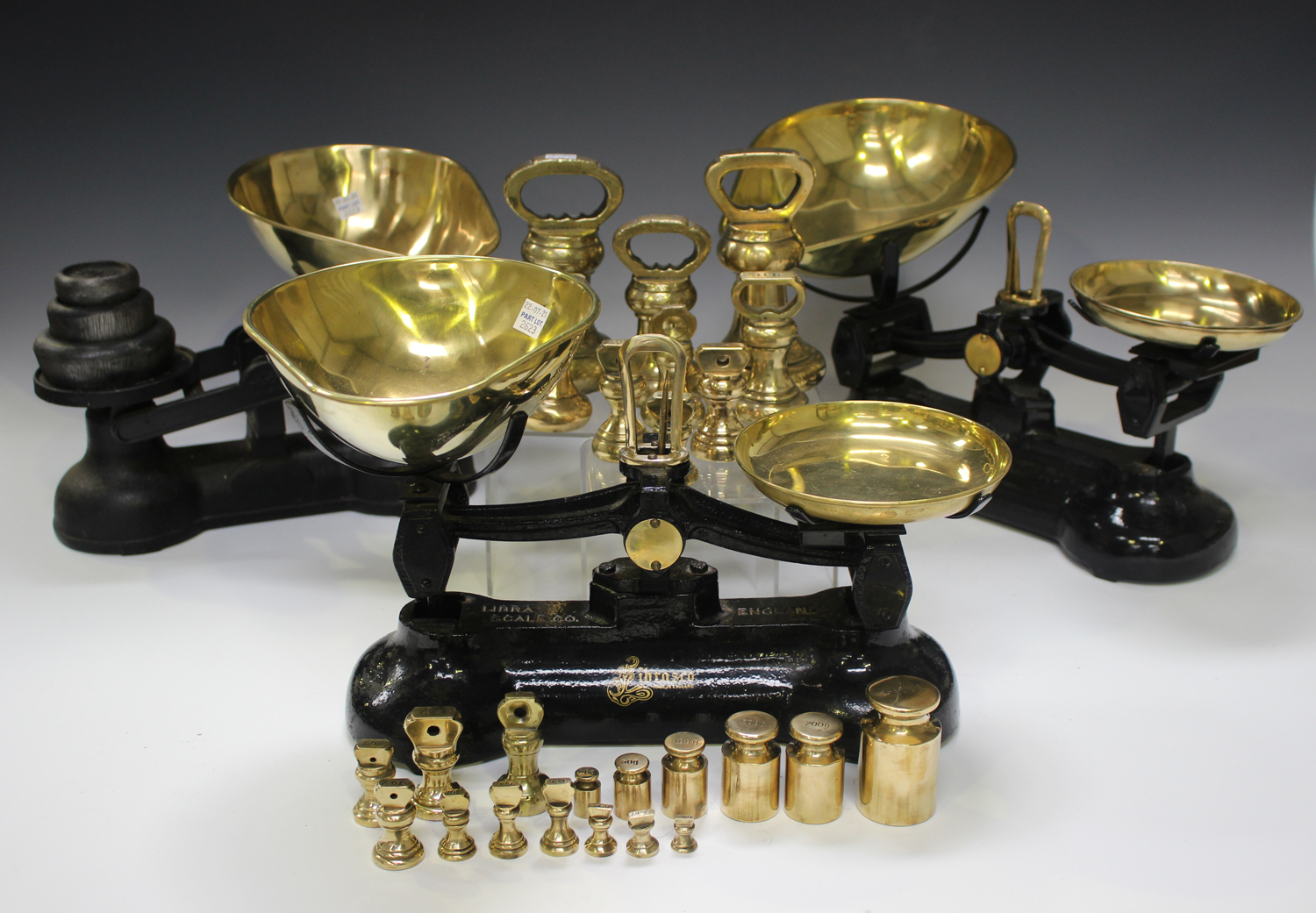 A group of three early 20th century cast iron balance scales with brass pans, together with a