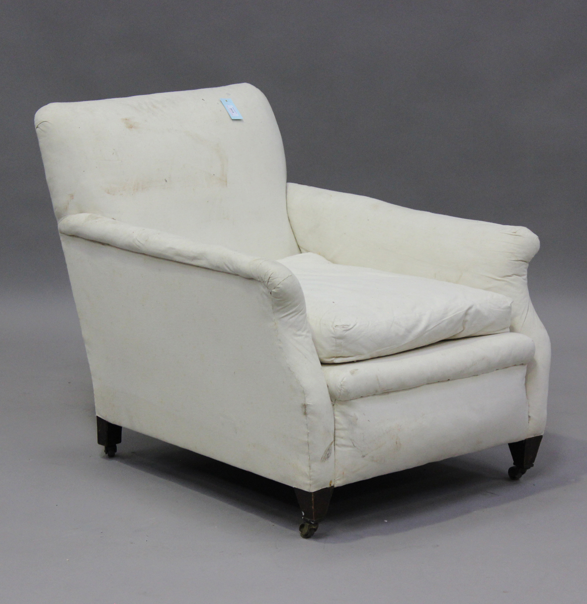 An Edwardian scroll armchair, in the manner of Howard & Sons, raised on square tapering legs, height