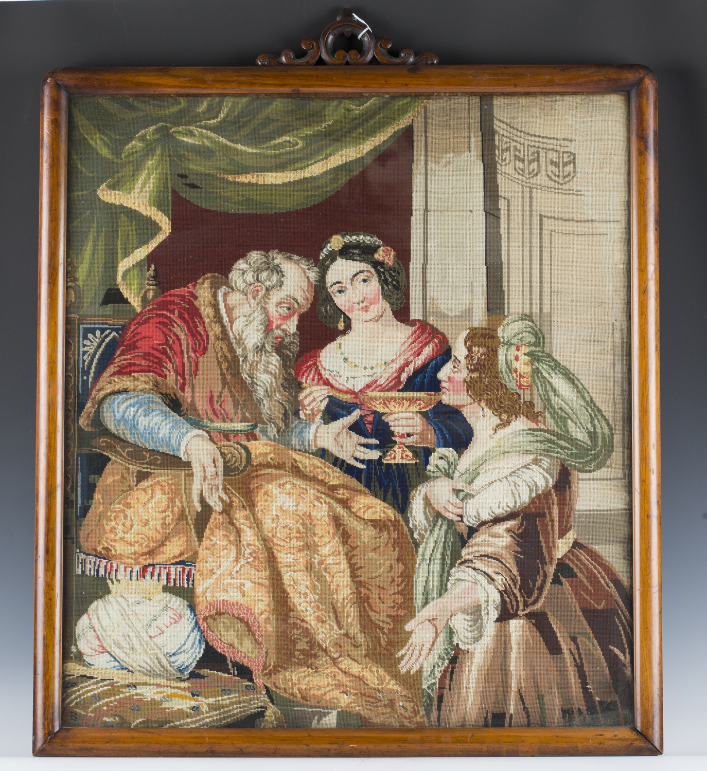 A Victorian Berlin woolwork panel depicting a seated king and two ladies, 75cm x 66cm, within a