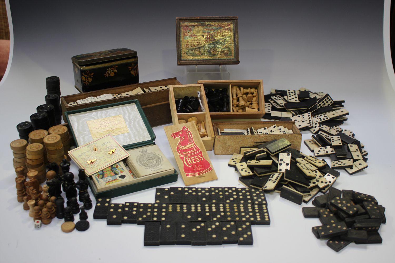 A quantity of bone and ebony dominoes, other sets of dominoes and various draught and chess pieces.