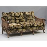 An early 20th century Queen Anne style walnut framed three-piece bergère suite, comprising a settee,