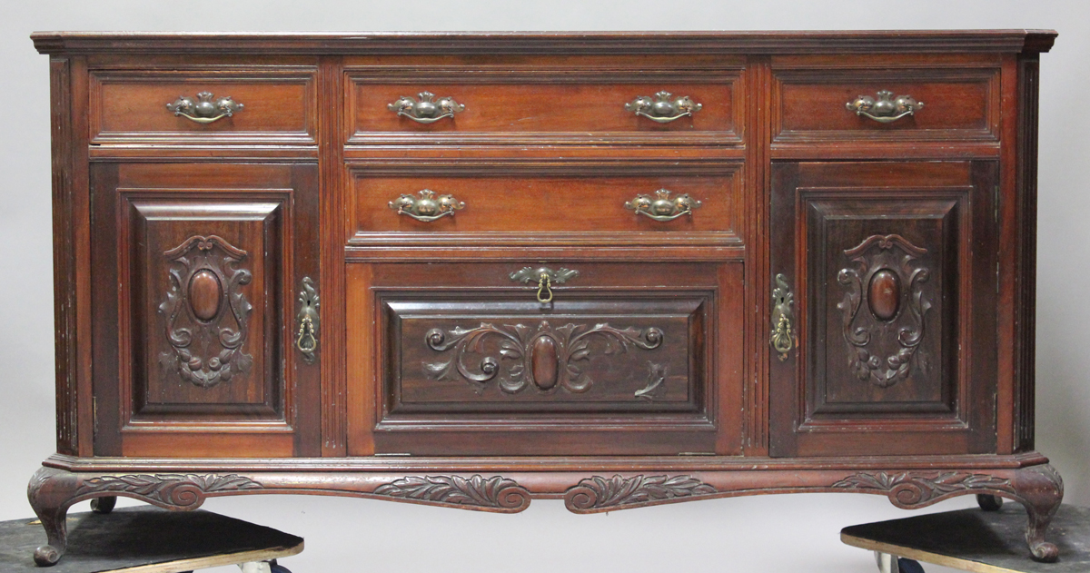 A late Victorian walnut sideboard with carved decoration, fitted with drawers and cupboards,