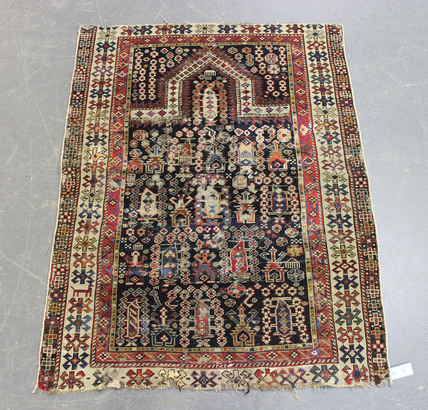 A Caucasian prayer rug, late 19th/early 20th century, the charcoal mihrab filled with boteh and