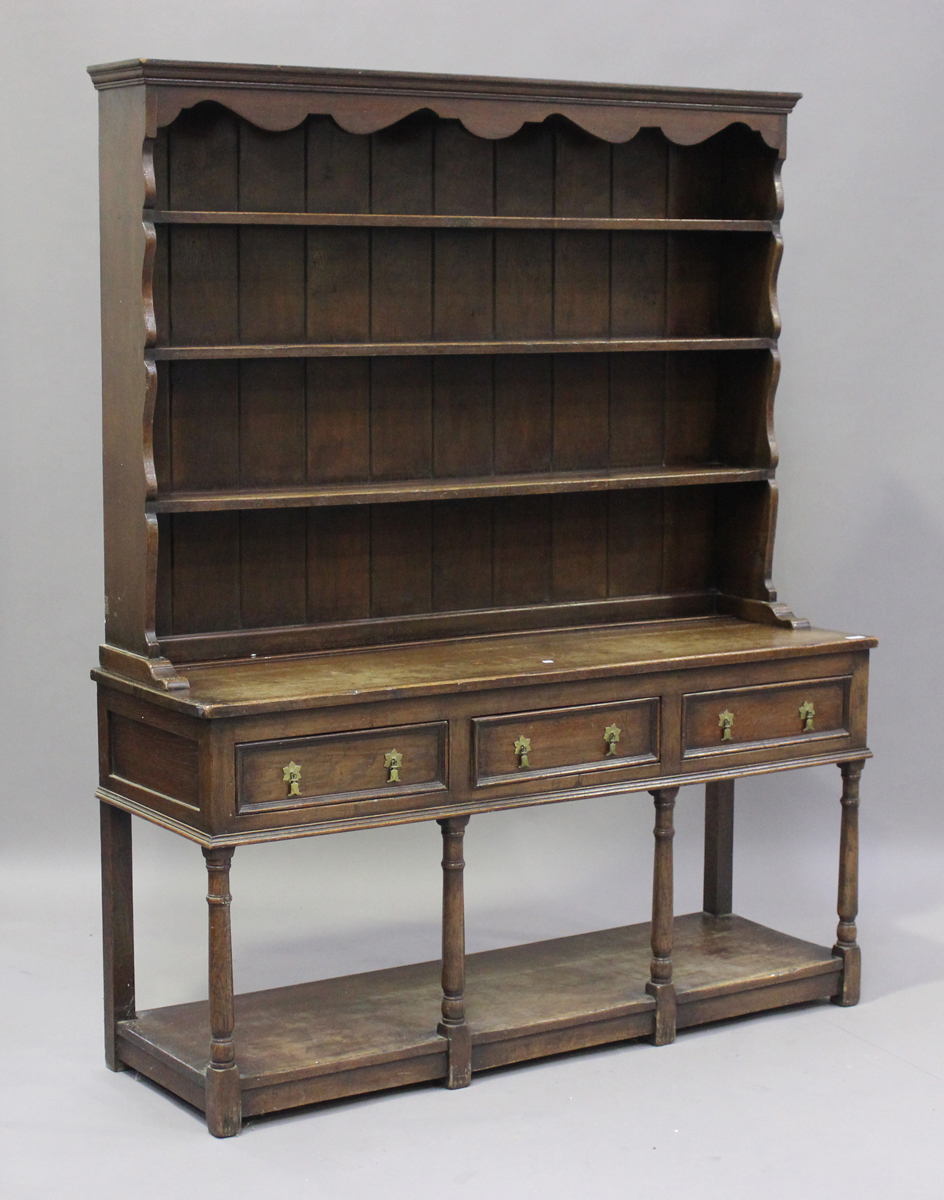 An early 20th century oak dresser, fitted with a plate rack above three drawers and a pot shelf,