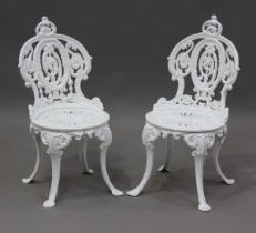 A pair of late Victorian white painted cast iron garden chairs of foliate scroll form, height