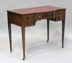 An Edwardian mahogany and boxwood inlaid writing table, fitted with five drawers, on square tapering