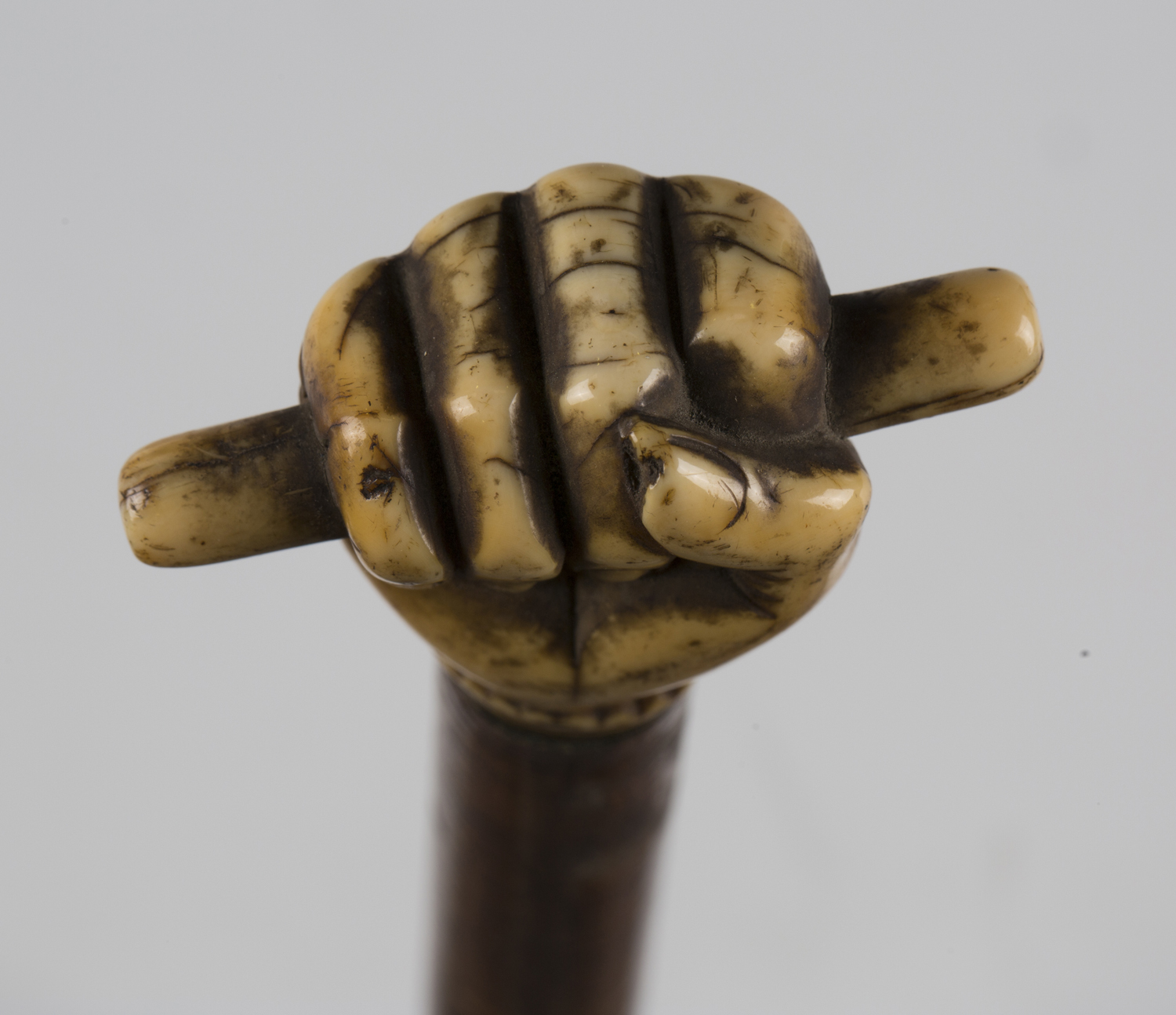 A 19th century sectional joined leather walking cane, the ivory handle carved as a hand holding a - Image 4 of 7