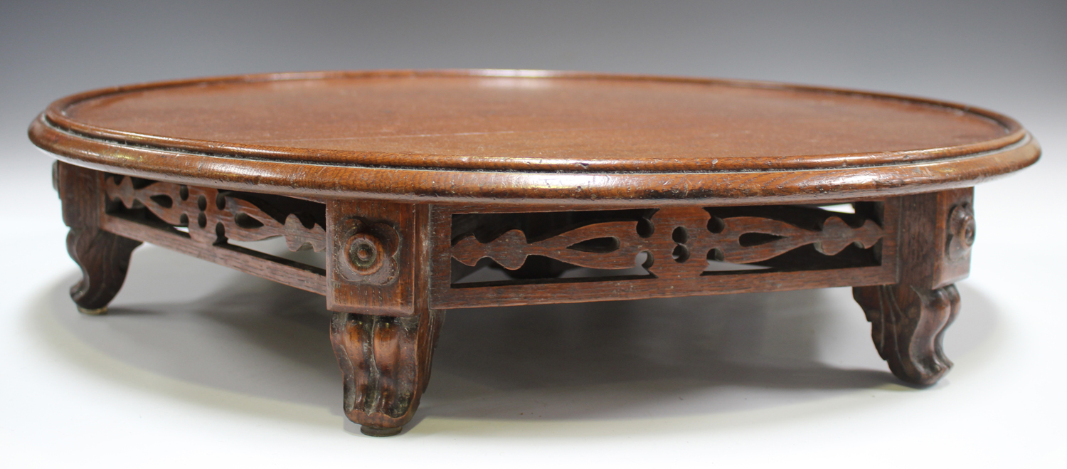 A late Victorian oak revolving lazy Susan, raised on a pierced frieze and scroll legs, height