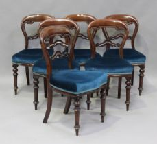 A set of six Victorian mahogany balloon back dining chairs, the overstuffed seats on turned legs,