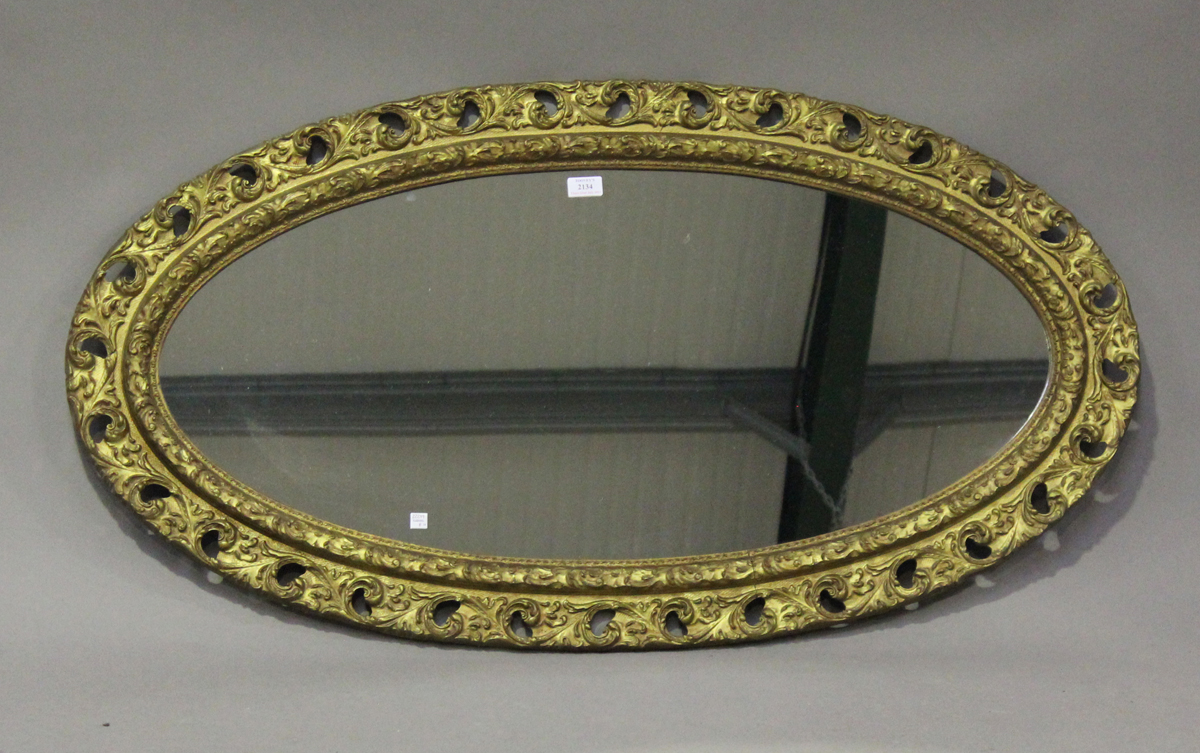An early 20th century gilt painted, carved and moulded oval wall mirror, 121cm x 65cm.Buyer's