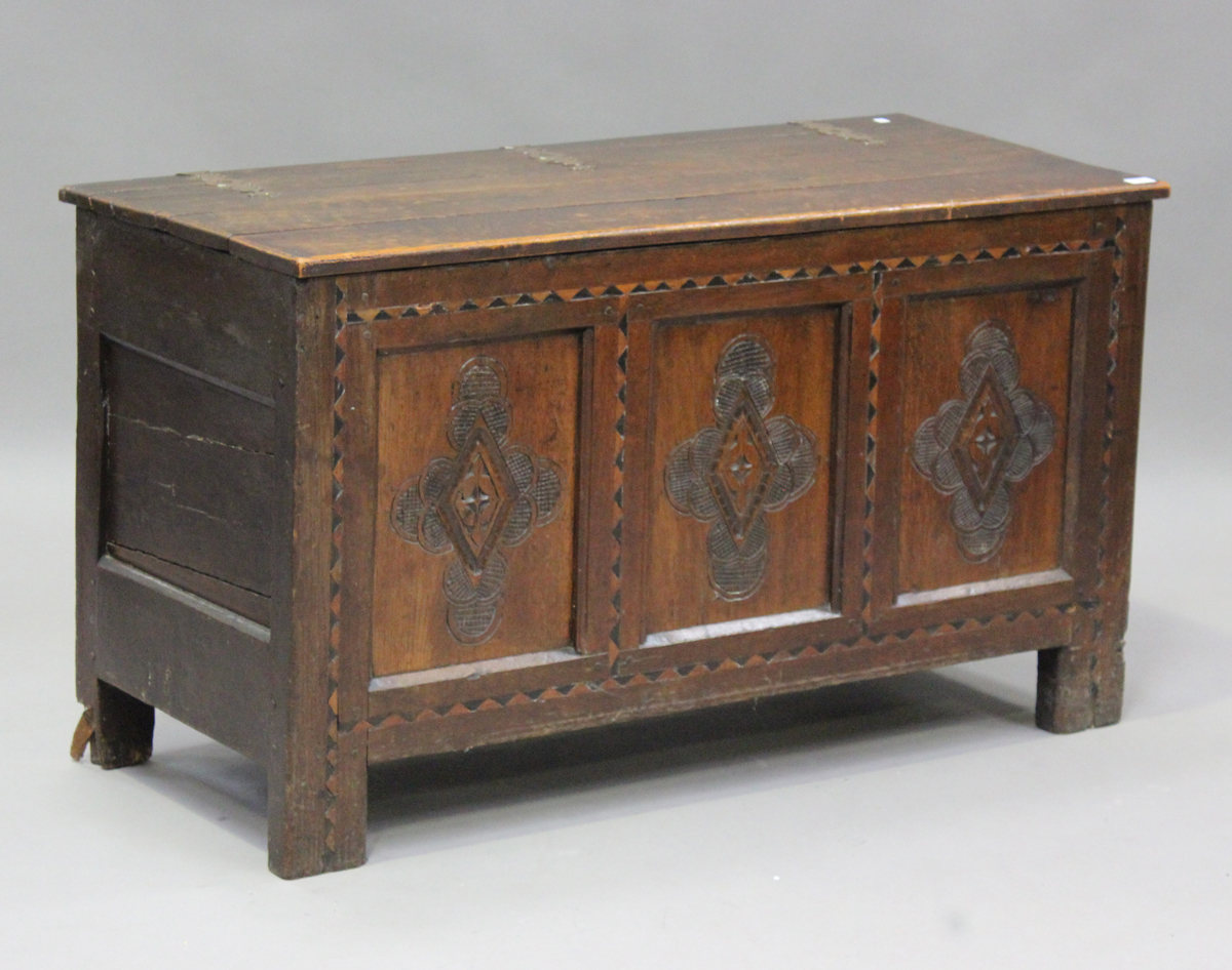 An early 18th century oak coffer with inlaid borders, the hinged lid above a triple panel front with