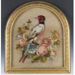 A Victorian woolwork and raised plush work arched panel, worked in coloured wools with a bird