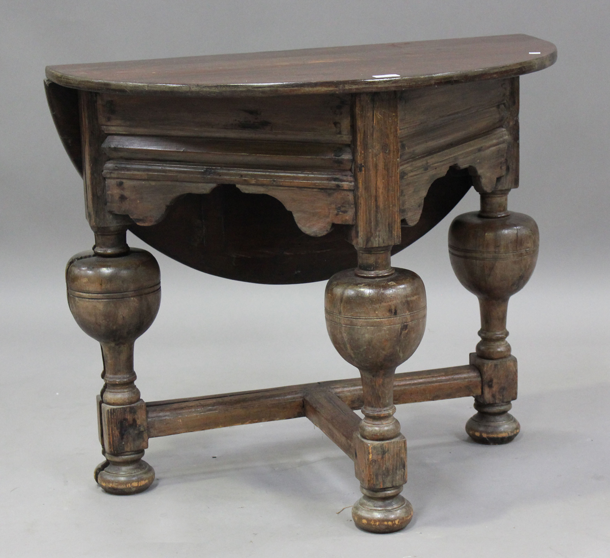 A 20th century Continental stained pine credence table, the drop-flap top raised on turned and block