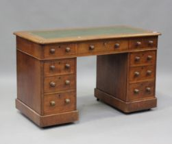 A late Victorian walnut twin pedestal desk, fitted with an arrangement of drawers, on plinth