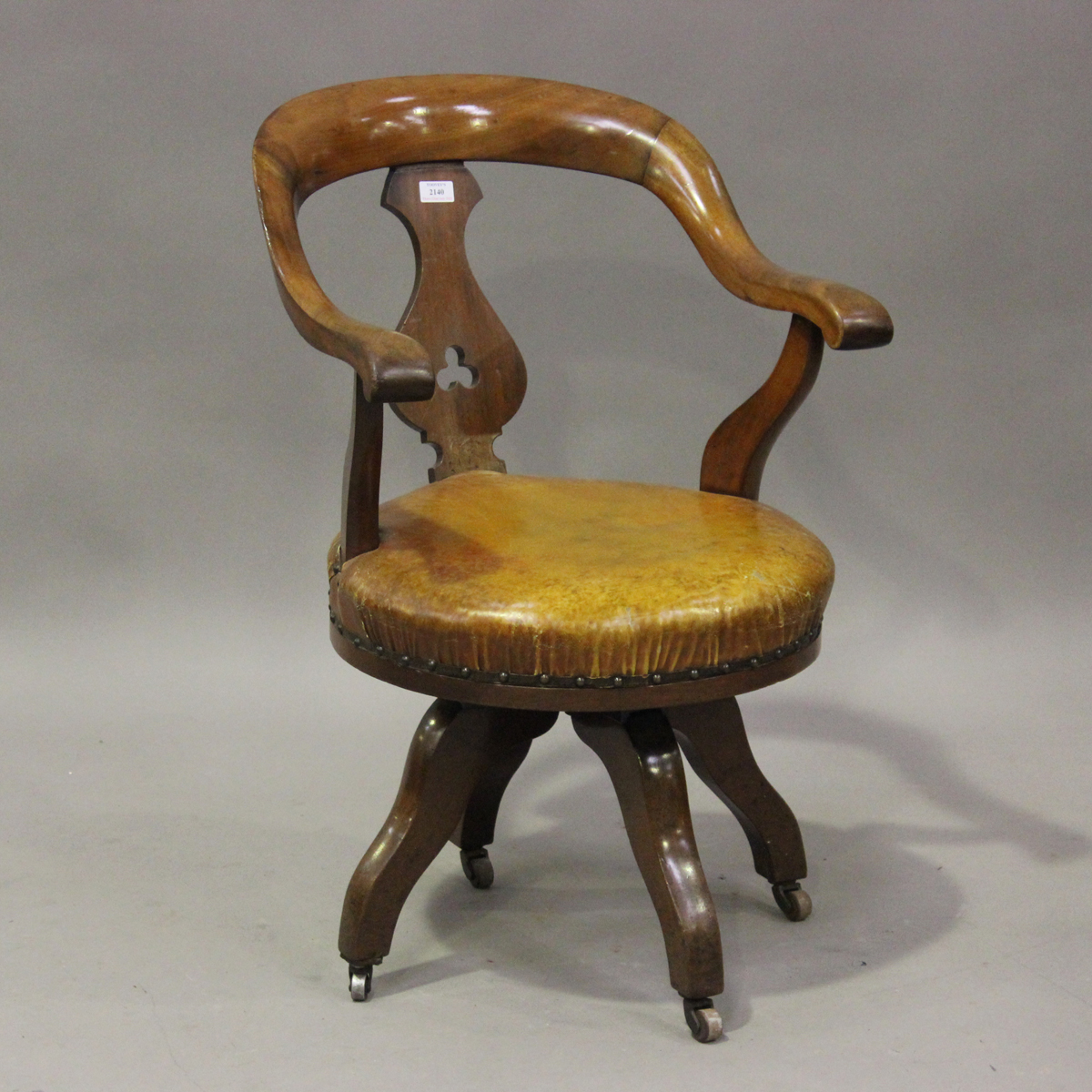 A late Victorian mahogany framed tub back revolving desk chair with a circular brown leather seat,