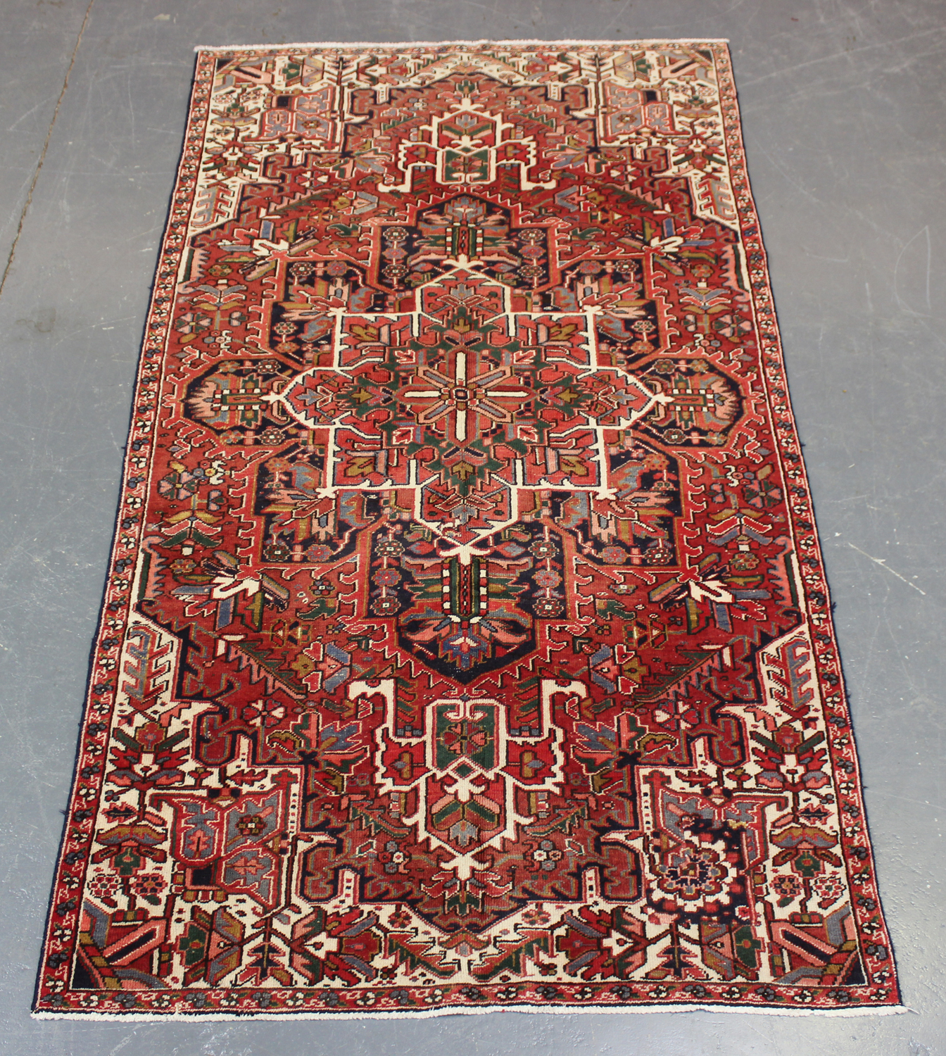 A Heriz rug, North-west Persia, mid-20th century, the terracotta field with a bold flowerhead