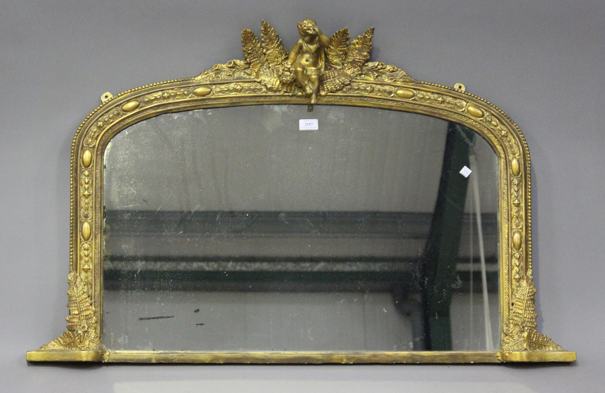 A late Victorian gilt painted overmantel mirror, the arched frame with putto and fern surmount,