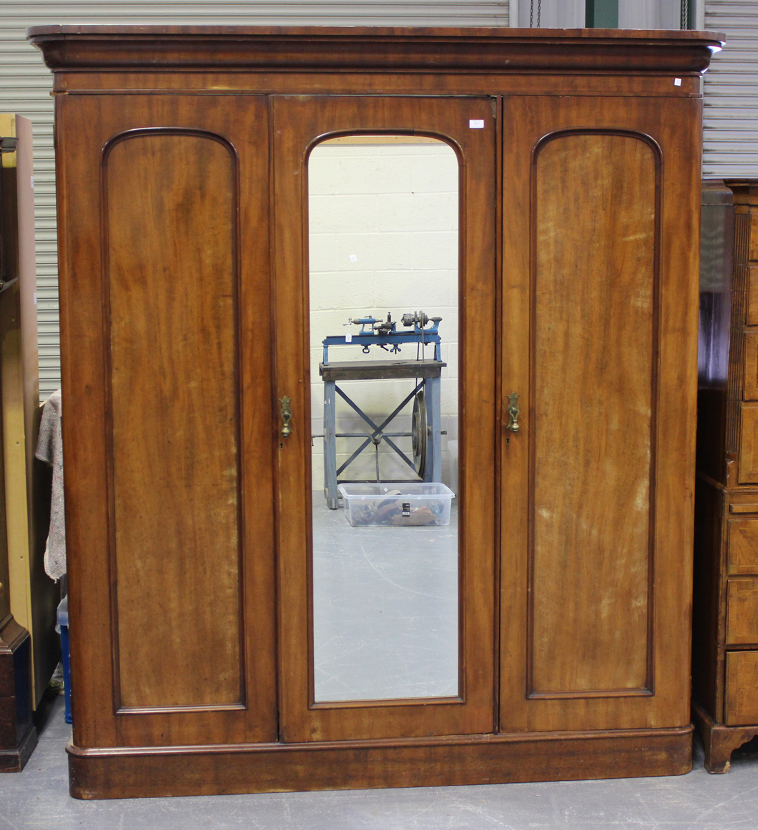 A late Victorian mahogany three-section wardrobe, fitted with panelled doors, height 215cm, width