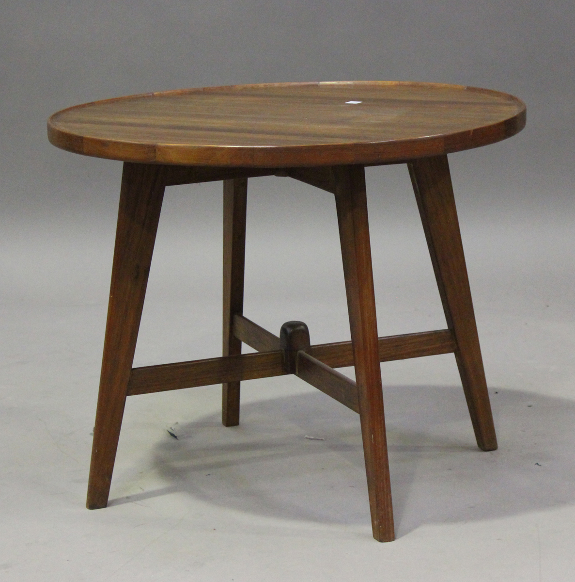 A mid-20th century teak circular occasional table of retro design, the planked top with raised edge,