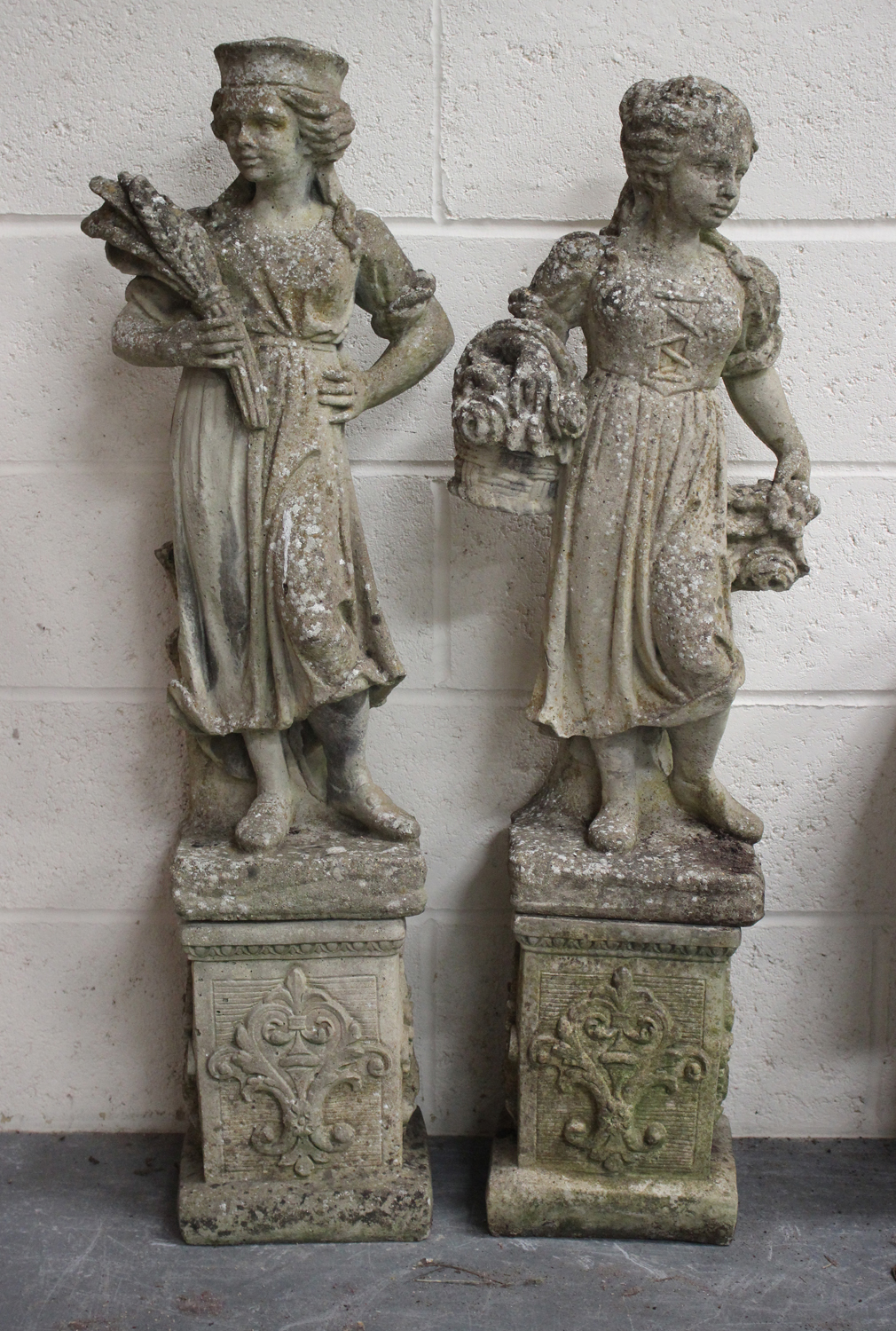 A near pair of late 20th century cast composition stone garden figures, raised on foliate