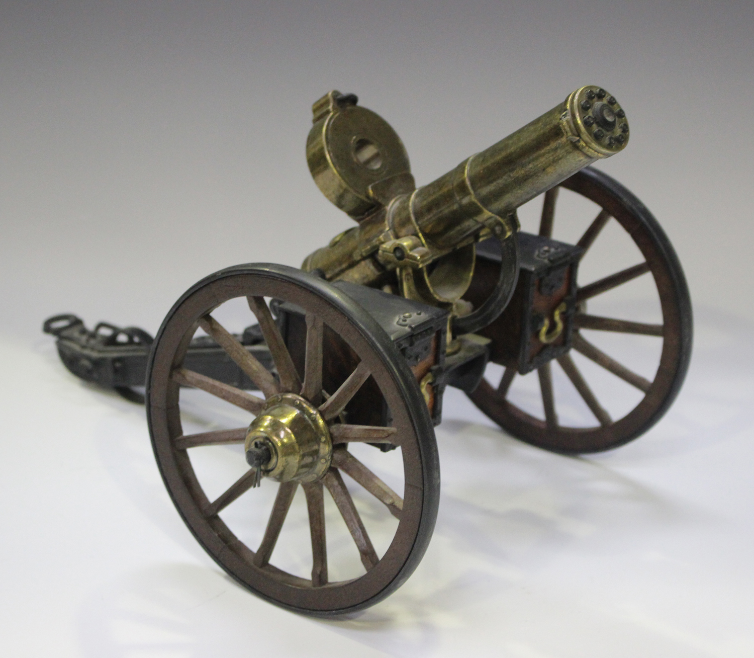 A late 20th century cast metal and wooden desk model of Gatling gun, mounted on a wheeled