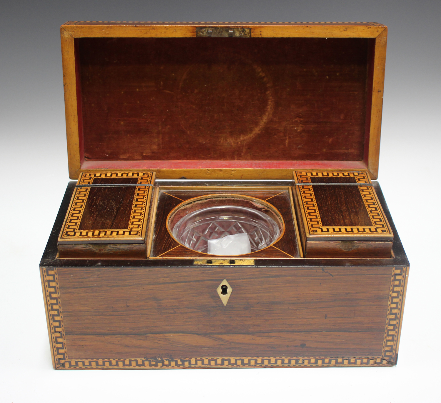 A George III rosewood tea caddy with inlaid running scroll borders and applied gilt metal phoenix