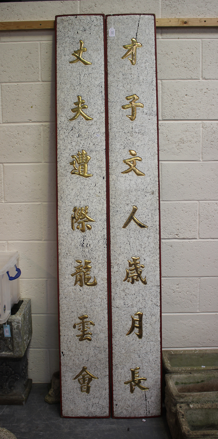 A pair of early/mid-20th century Chinese wooden panels, each with carved gilt characters on a
