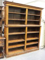 A Victorian oak open library bookcase, the moulded pediment above adjustable shelves, on a plinth