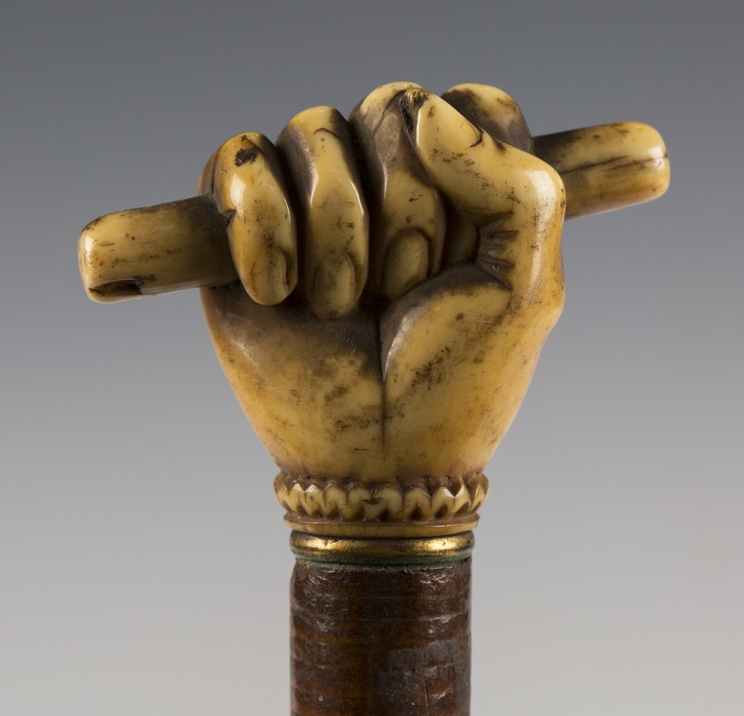 A 19th century sectional joined leather walking cane, the ivory handle carved as a hand holding a