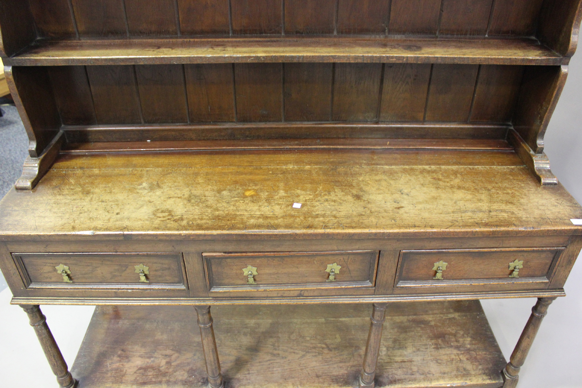 An early 20th century oak dresser, fitted with a plate rack above three drawers and a pot shelf, - Image 6 of 6