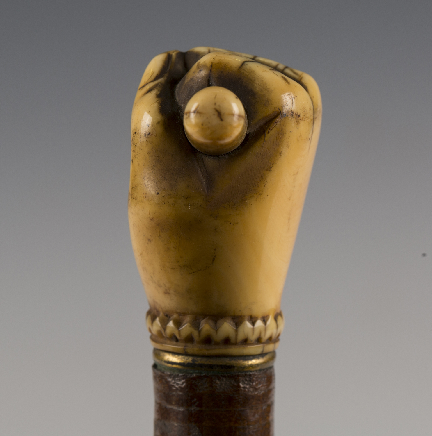 A 19th century sectional joined leather walking cane, the ivory handle carved as a hand holding a - Image 5 of 7