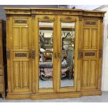 An Edwardian pale oak four-section wardrobe, the doors with carved foliate panels, enclosing sliding