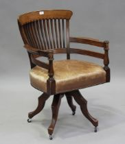 An Edwardian walnut framed comb back revolving desk chair with a brown leather seat, height 90cm,